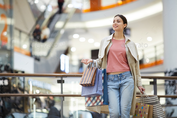 Content woman searching for sale in mall - Stock Photo - Images