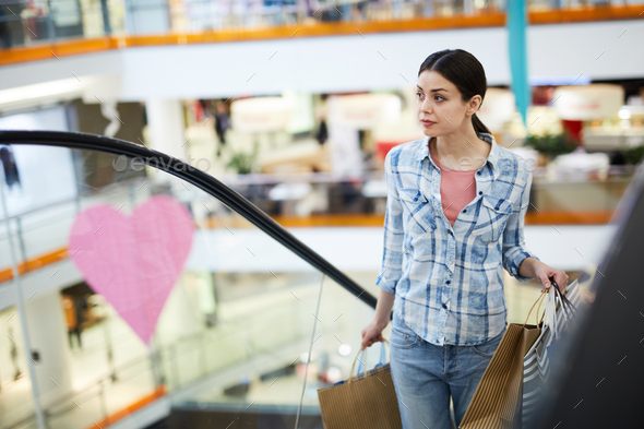 Young woman with shopping bags moving up escalator - Stock Photo - Images