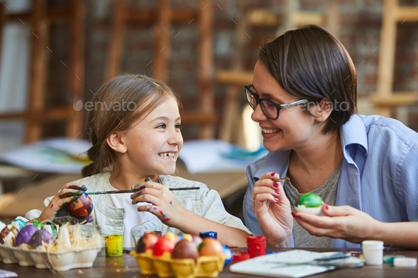 Little Girl Painting Easter Eggs with Mom - Stock Photo - Images