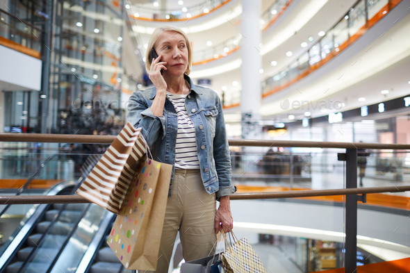 Mature woman calling friend in shopping mall - Stock Photo - Images
