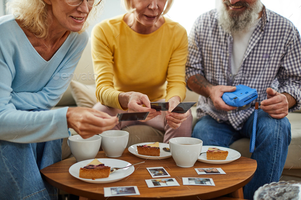 Friends viewing photos over tea - Stock Photo - Images