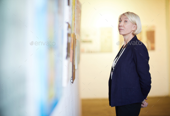 Mature Woman Looking at Paintings - Stock Photo - Images