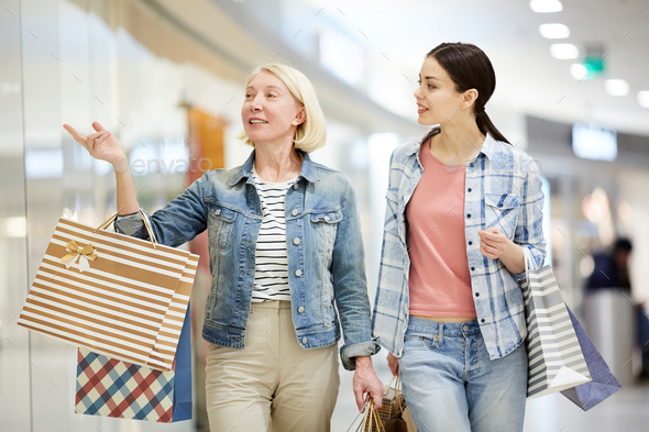 Blond lady recommending clothing store to daughter - Stock Photo - Images