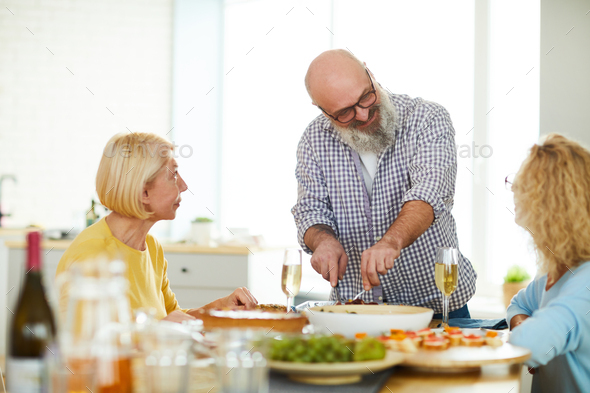 Content mature man cutting meat for guests - Stock Photo - Images