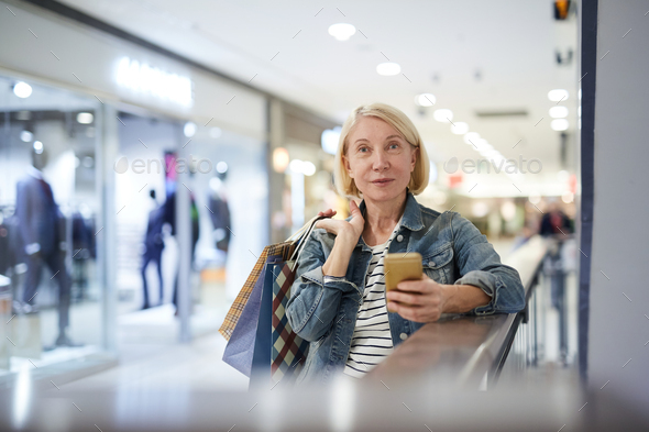 Attractive mature lady sending photo message to friend during shopping - Stock Photo - Images