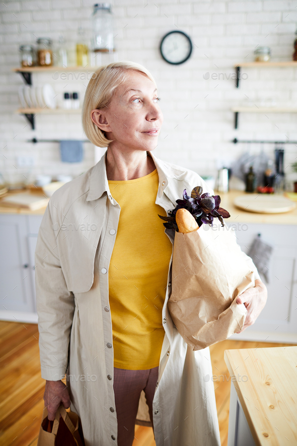 Lady with full bags in kitchen - Stock Photo - Images