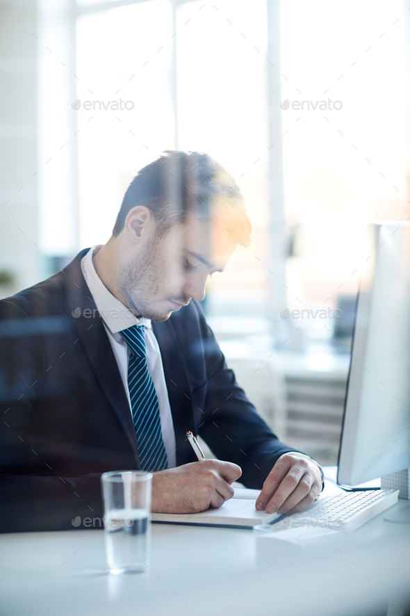 Making notes by desk - Stock Photo - Images