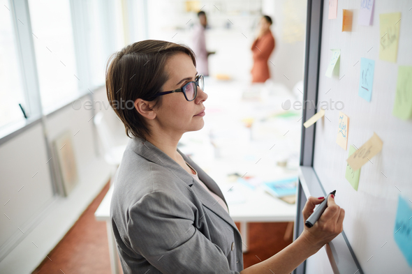 Businesswoman Writing on Whiteboard - Stock Photo - Images