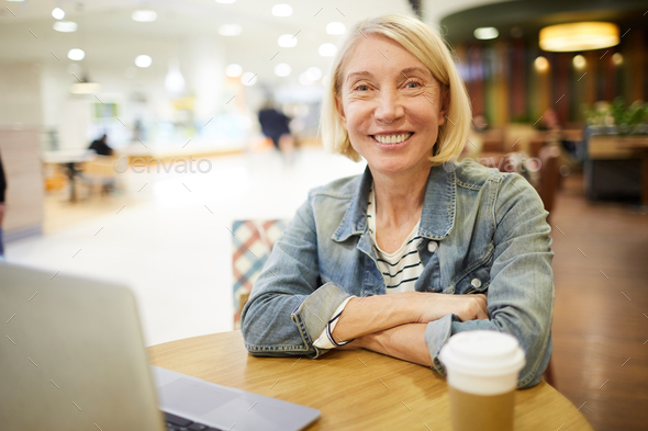 Cheerful freelance woman working in cafe - Stock Photo - Images