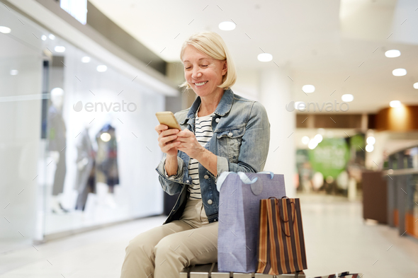 Happy woman making post about shopping on social media - Stock Photo - Images