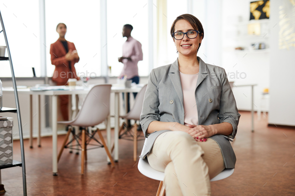 Smiling Businesswoman Sitting on Chair - Stock Photo - Images