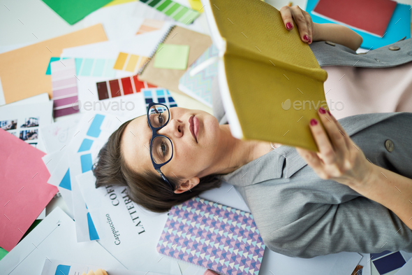 Businesswoman Reading Book on Floor - Stock Photo - Images