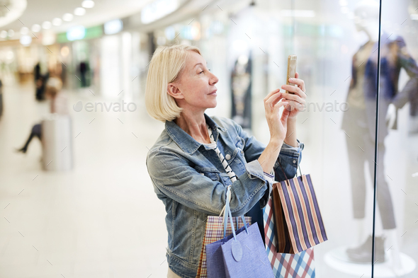 Content woman photographing favorite outfit in mall - Stock Photo - Images