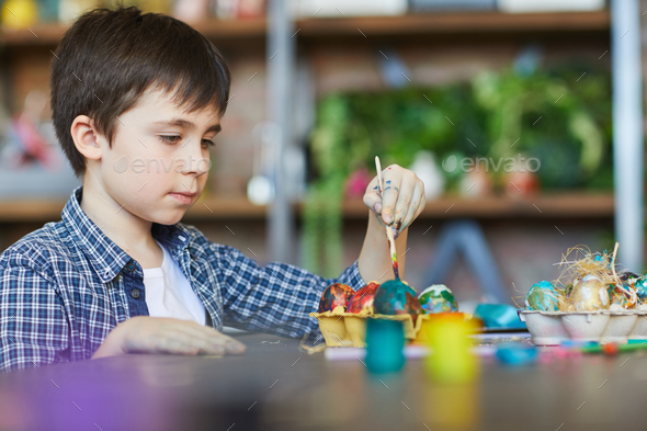 Cute Boy Painting Eggs for Easter - Stock Photo - Images