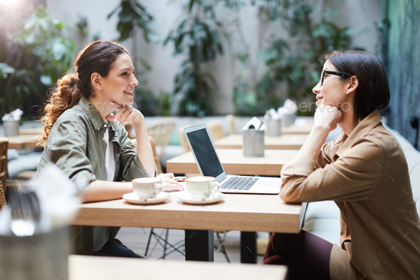 Business ladies discussing project in cafe - Stock Photo - Images