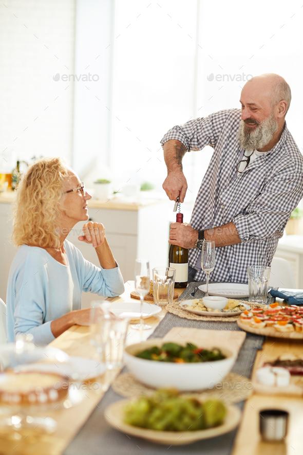 Cheerful senior man opening wine bottle - Stock Photo - Images