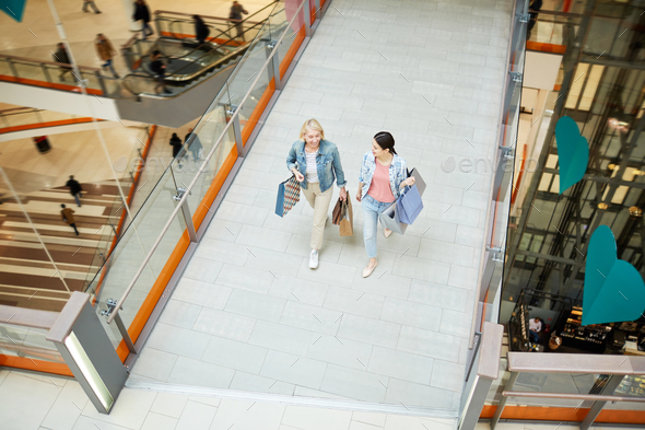 Excited mother and daughter talking while walking over mall - Stock Photo - Images