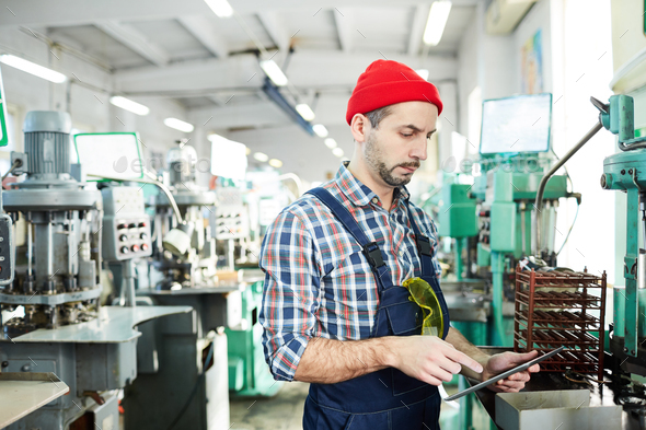 Mature Factory Worker Using Tablet by Machines - Stock Photo - Images