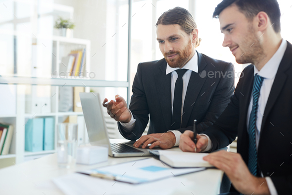 Men discussing online data - Stock Photo - Images