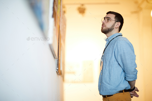 Bearded Man Looking at Paintings in Art Gallery - Stock Photo - Images