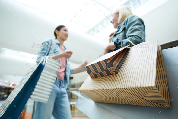 Colorful paper shopping bags in hands of customers - Stock Photo - Images