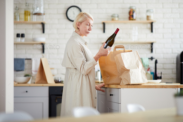 Mature lady unpacking paper bags in kitchen - Stock Photo - Images