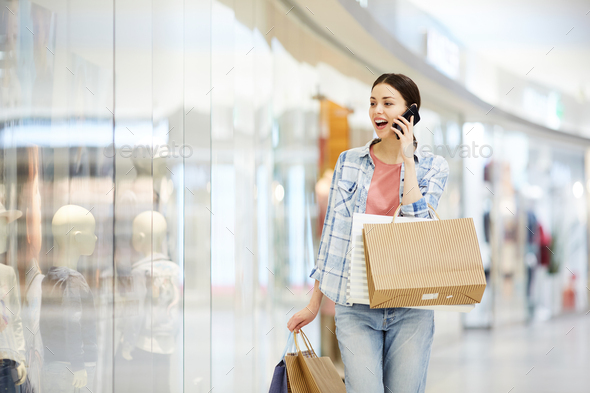 Shocked lady shopaholic talking on phone - Stock Photo - Images