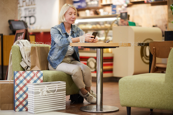 Lady drinking water in food court - Stock Photo - Images