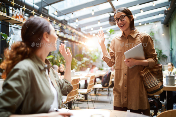 Excited women greeting each other in cafe - Stock Photo - Images