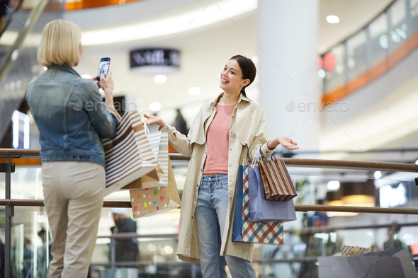 Lady photographing friend with plenty shopping bags - Stock Photo - Images