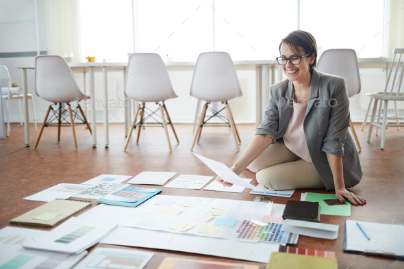 Cheerful Businesswoman Planning Project on Floor - Stock Photo - Images