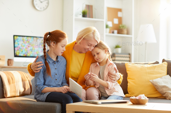 Mature Mother Embracing Two Girls - Stock Photo - Images