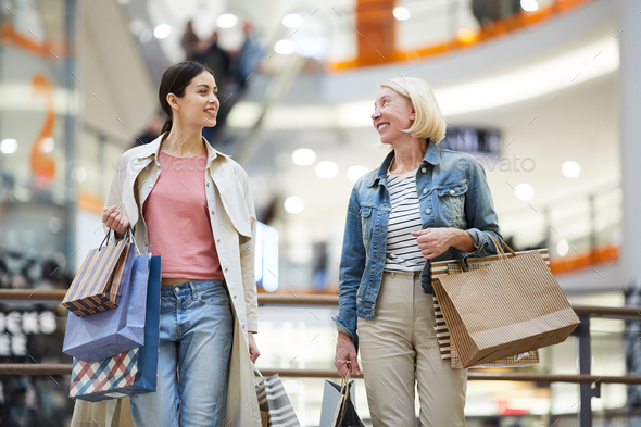 Cheerful women sharing expressions from shopping - Stock Photo - Images