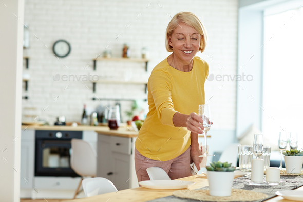Smiling woman putting flute on table - Stock Photo - Images