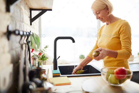 Happy woman cleaning fruits - Stock Photo - Images