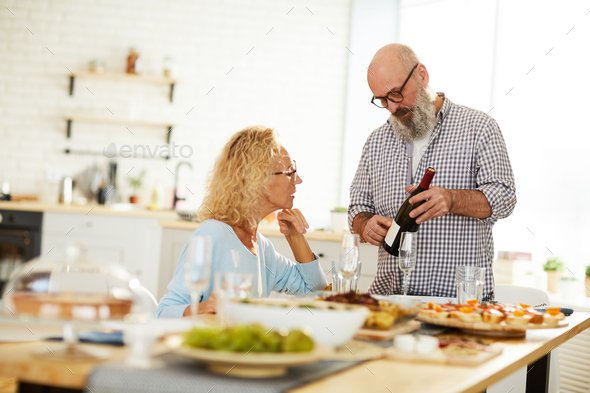 Senior man talking about wine to lady - Stock Photo - Images
