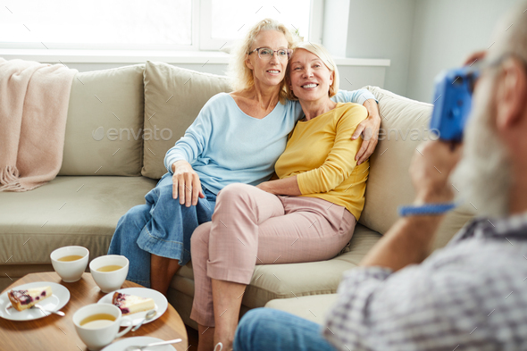 Happy ladies friends hugging on sofa - Stock Photo - Images