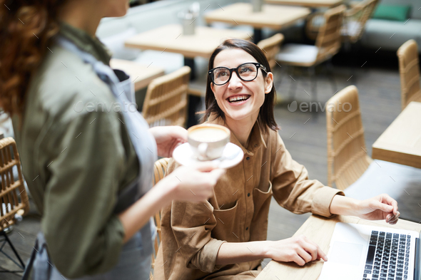 Businesswoman talking to waitress in cafe - Stock Photo - Images