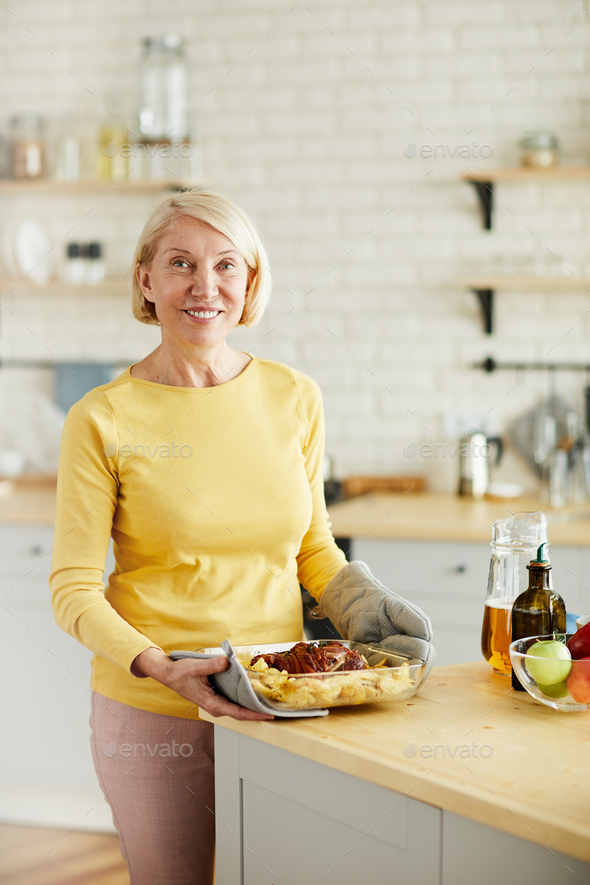Mature woman satisfied with her cooked dish - Stock Photo - Images