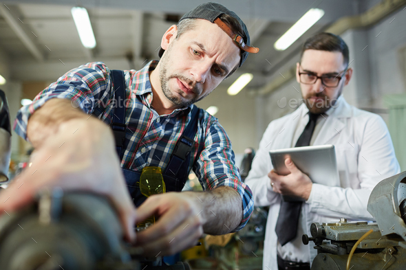 Repairman Fixing Machines at Factory - Stock Photo - Images
