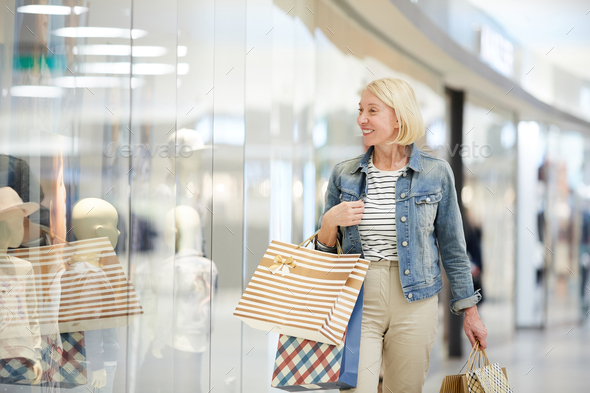 Jolly woman looking at shop-windows - Stock Photo - Images