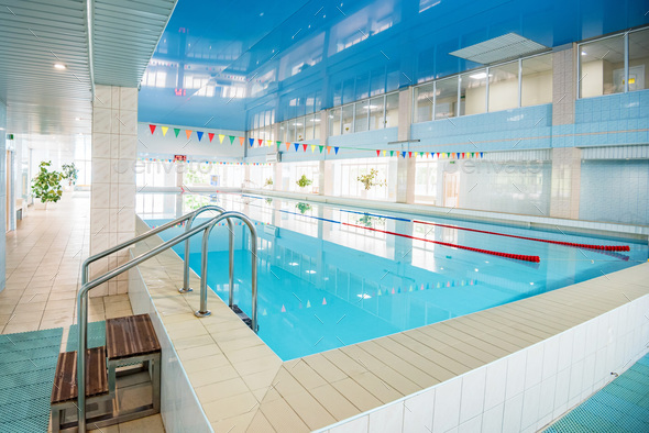 View of indoors swimming pool with metal ladder - Stock Photo - Images