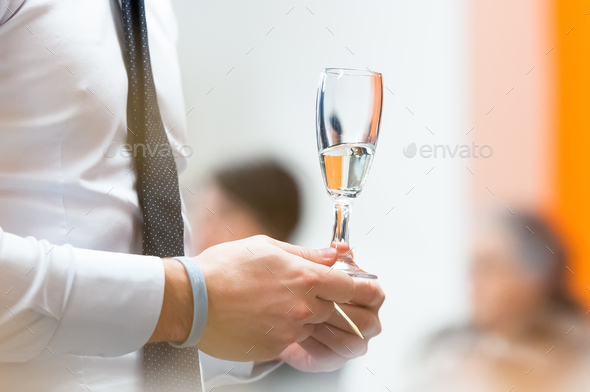 Glass of champagne in hand - Stock Photo - Images