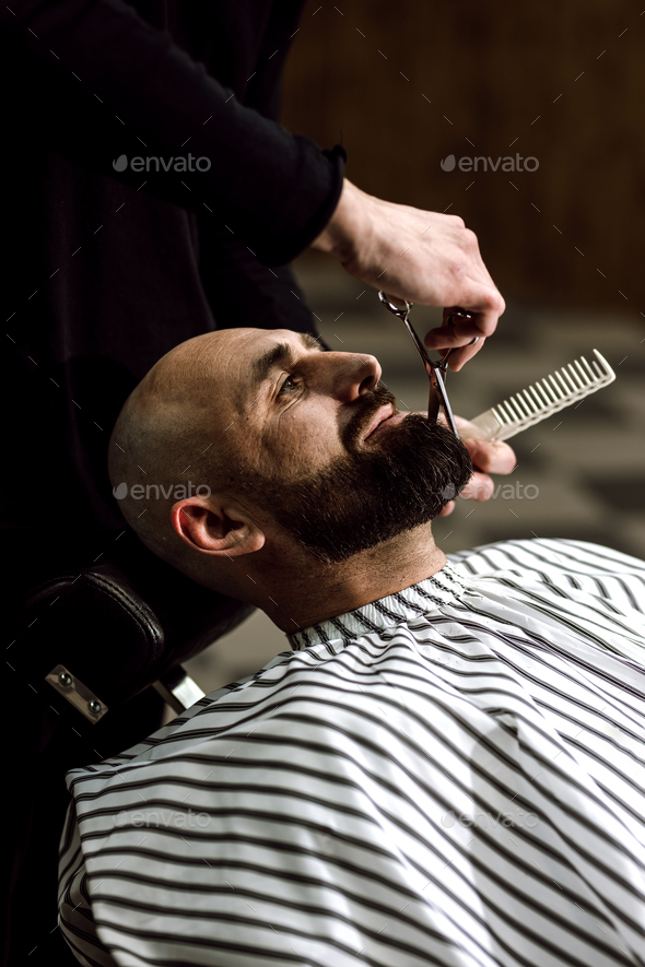 Men's fashion. The barber scissors beard of brutal man in the stylish barbershop - Stock Photo - Images