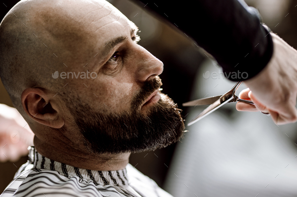 Fashion barber dressed in a black clothes scissors beard of brutal man in the stylish barbershop - Stock Photo - Images