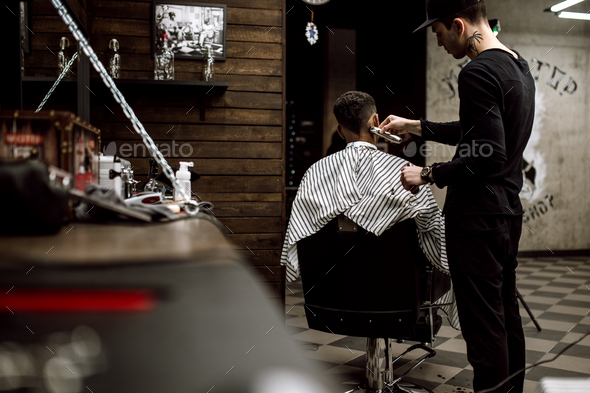 The fashion barber dressed in black clothes makes a razor cut hair for a stylish black-haired man in - Stock Photo - Images