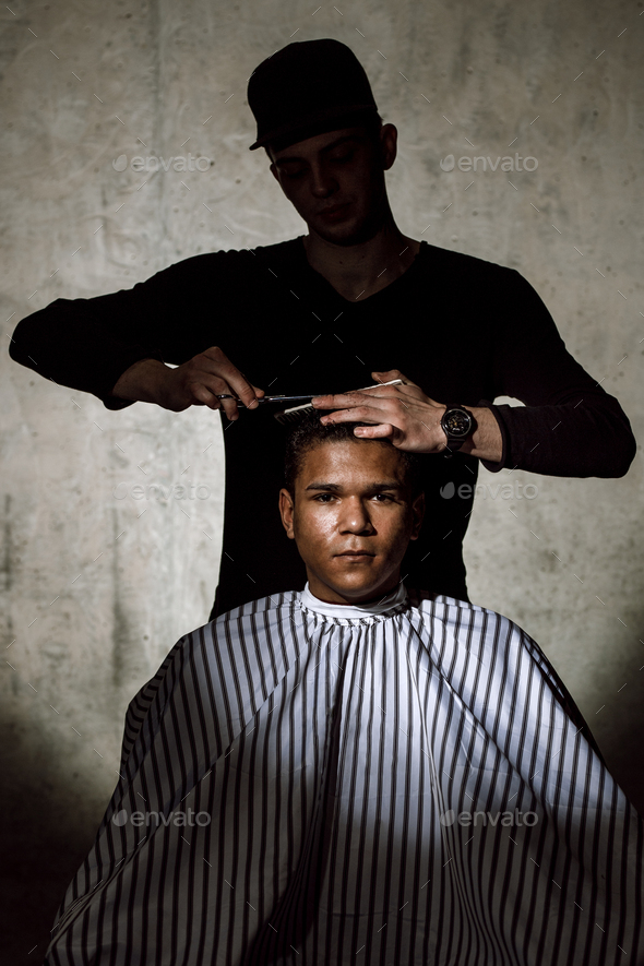 The stylish barber dressed in black clothes scissors the man's hair in a barbershop against a - Stock Photo - Images