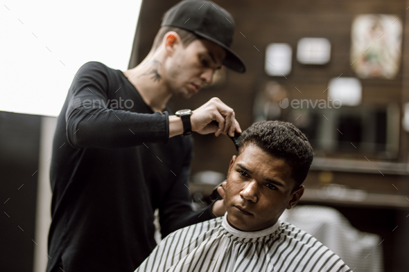 The barber dressed in black clothes makes a razor cut hair back and sides for a stylish man sitting - Stock Photo - Images