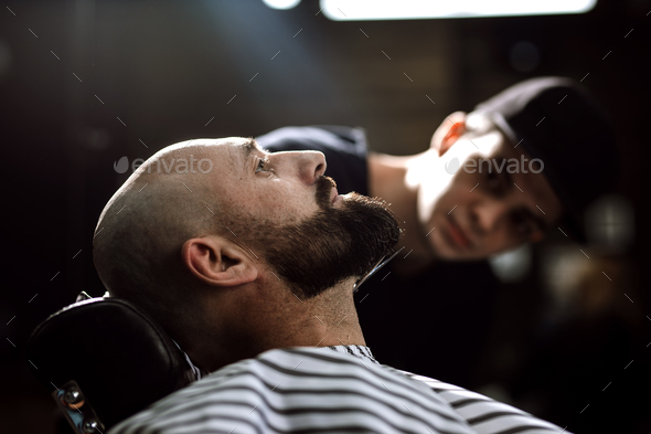 Fashion barber dressed in a black clothes tidies up men's beard and scissors it in the - Stock Photo - Images