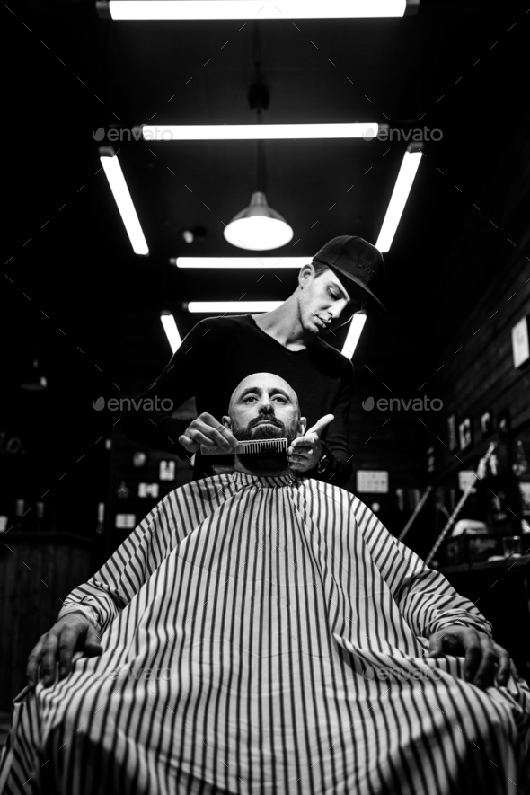 Black and white. The stylish barbershop. The fashion barber tidies up beard of brutal man sitting in - Stock Photo - Images